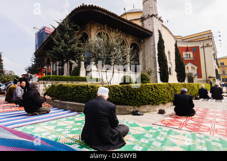 Muslim men praying in the street outside Et'hem Bey Mosque. Tirana, Albania - Stock Photo