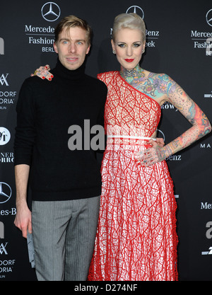 Designer Sebastian Ellrich and Austrian tattoo model Lexy Hell arrives at the Marc Stone show during the Mercedes - Stock Photo
