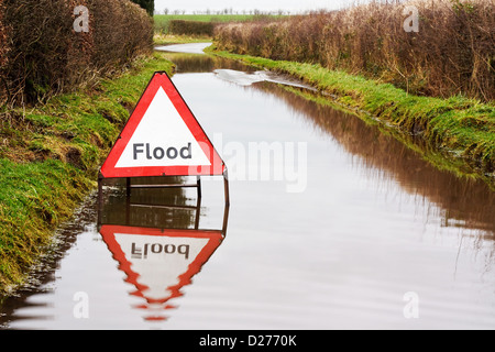 Flood warning sign on a flooded country road - Stock Photo