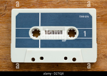 blank vintage cassette from early 80's on red wood background - Stock Photo