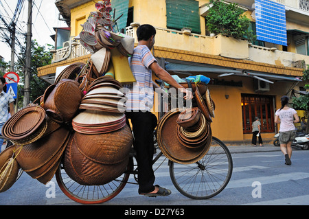 Man on a bicycle selling straw bowls and hats, Hanoi, Vietnam - Stock Photo