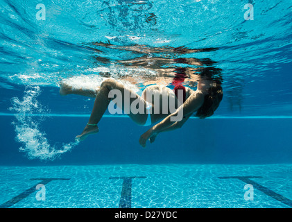 Pregnant woman exercising in a swimming pool. - Stock Photo