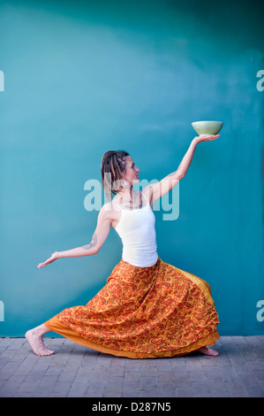 Unique woman in a dancing yoga posture offering up a beautiful ceramic bowl against the backdrop of a blue wall. - Stock Photo