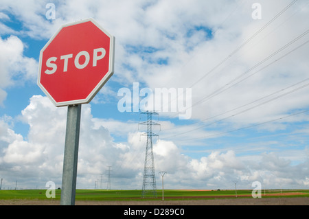Stop traffic sign against cloudy sky, and landscape with power lines. - Stock Photo