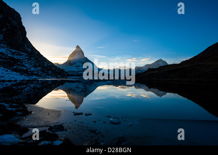 Matterhorn and Dente Blanche from Riffelsee mountain lake above Zermatt, Switzerland - Stock Photo