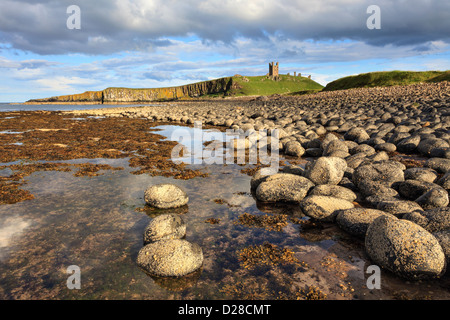 Dunstanburgh Castle captured from Greymare Rocks at the southern end of Embleton Bay in Northumberland.  The composition - Stock Photo