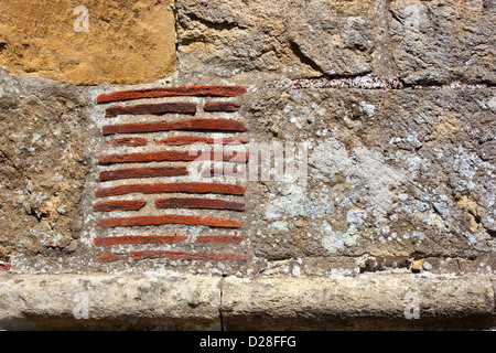 Background and texture of architectural detail with an ancient wall made from stone blocks and clay tiles. - Stock Photo