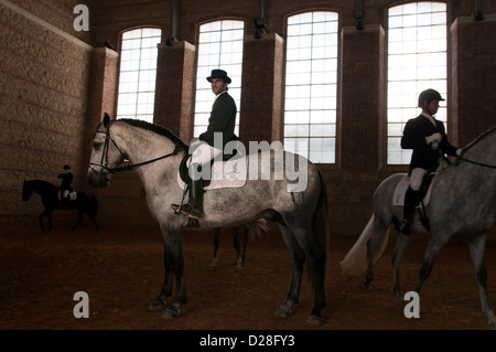 Jockeys warming up in a stables before a horse race - Stock Photo