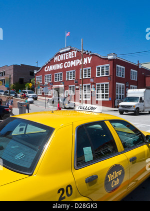CANNERY ROW Monterey Canning Company building Cannery Row with yellow taxi cab in foreground Monterey California - Stock Photo