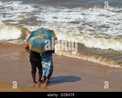 A young couple seeking privacy on the beach in Sri Lanka shelter beneath a parasol  as they enjoy each other's company - Stock Photo
