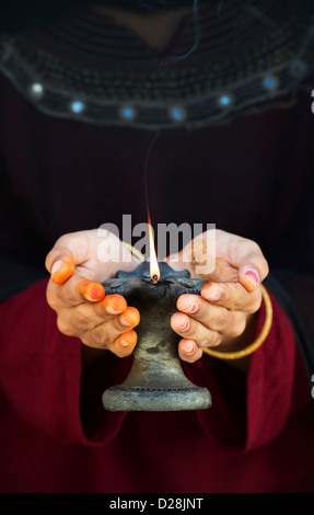 Teenage Indian girl holding a lit oil lamp - Stock Photo