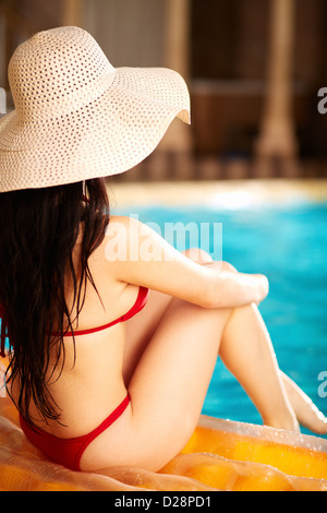 Back view of lovely woman in bikini and hat sitting on mattress - Stock Photo