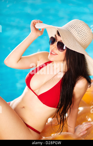 Portrait of lovely woman in bikini and hat sitting on mattress - Stock Photo