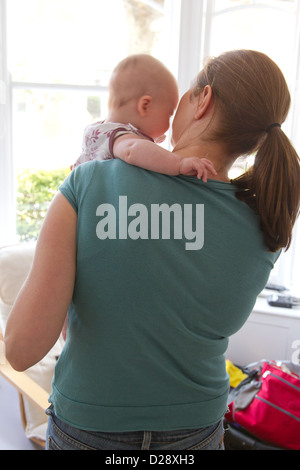 Mother & baby looking out of window - Stock Photo