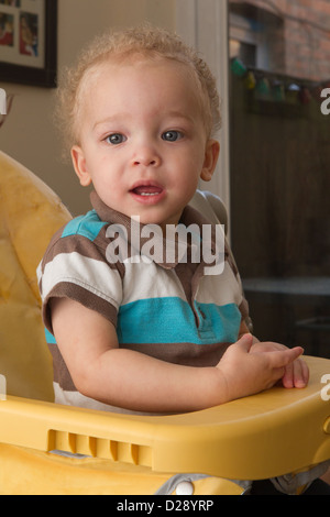 Toddler in high chair - Stock Photo