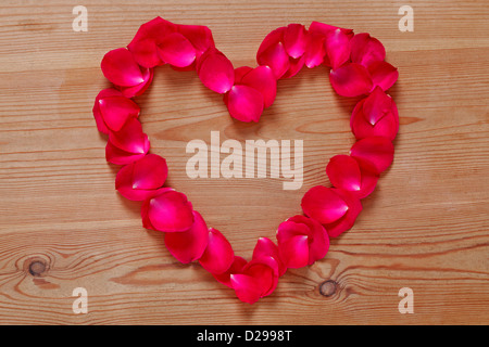 Heart shape made from red rose petals placed upon on a rustic wooden background. - Stock Photo