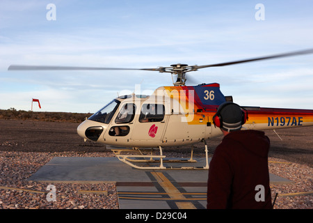 crew member watches papillon helicopter tour full of passengers take off from helipad at Grand canyon west airport - Stock Photo
