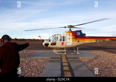 crew member gives thumbs up for take off to papillon helicopter tour full of passengers Grand canyon west airport - Stock Photo