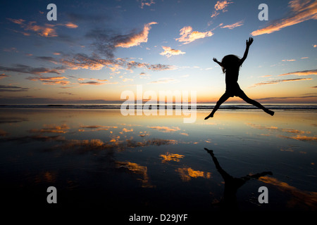 Little girl jumping at sunset on a beach at low tide - Stock Photo