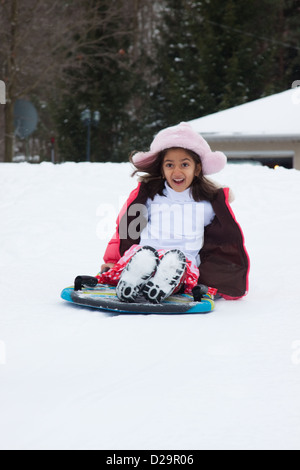 A happy East Indian girl goes down a slope on a toboggan - Stock Photo