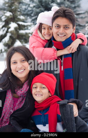 A beautiful East Indian parents play with her children in the snow. - Stock Photo