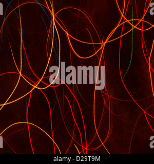 Red and orange light trails against a black background - Stock Photo