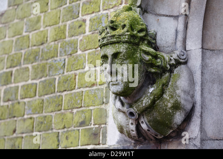 Detail of a historic building in Winchester with a carved stone figure head on the wall - Stock Photo
