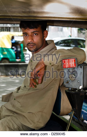 An Indian tuk tuk driver waits for a fare in his rickshaw, Bangalore, India - Stock Photo