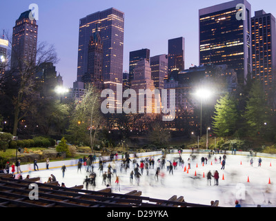 Wollman Rink Ice Skating in Central Park with Manhattan Skyline in background, NYC - Stock Photo