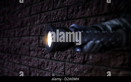 gloved hand holding a lit flashlight in the dark beside a brick wall. Low key. - Stock Photo
