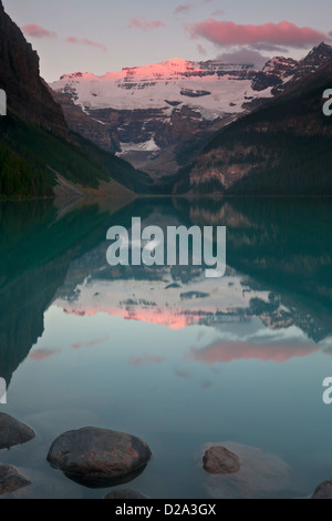 Morning alpenglow on Mount Victoria reflected in Lake Louise, Banff National Park, Canadian Rockies, Alberta, Canada. - Stock Photo