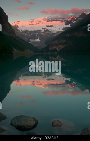 Morning alpenglow on Mount Victoria with pink clouds above reflected in Lake Louise, Banff National Park, Canadian - Stock Photo