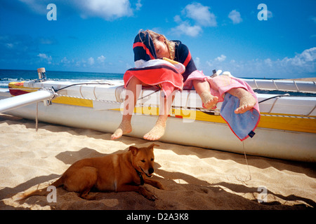 Girls (4 And 6) Playing On Beached Outrigger Sailing Canoe With Dog Resting In The Shade. North Shore Oahu, Hawaii. - Stock Photo