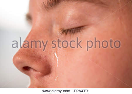 close up of a young woman with a tear running down her face. - Stock Photo