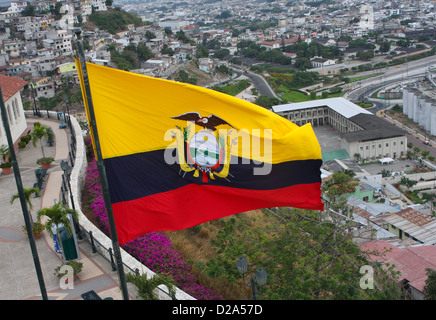 An Ecuadorian flag with yellow, blue and red strips flying over a city in Ecuador, South America - Stock Photo