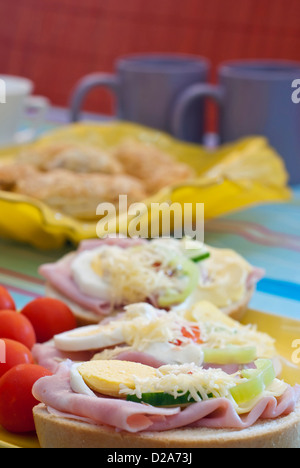 Served rich breakfast. Sandwiches with tomatoes. - Stock Photo