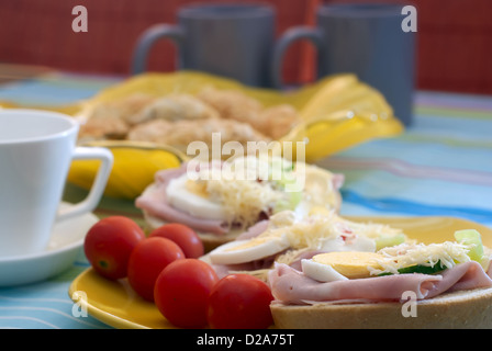 Delicious sandwiches with tomatoes, ham, eggs and grated cheese. - Stock Photo
