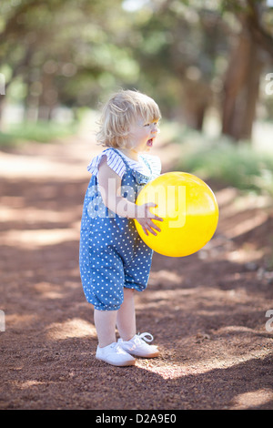 Toddler girl with ball on dirt road - Stock Photo
