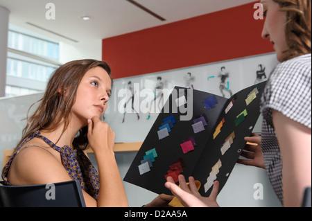 Businesswomen examining fabric swatches - Stock Photo