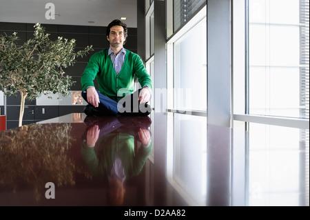 Businessman meditating on table - Stock Photo