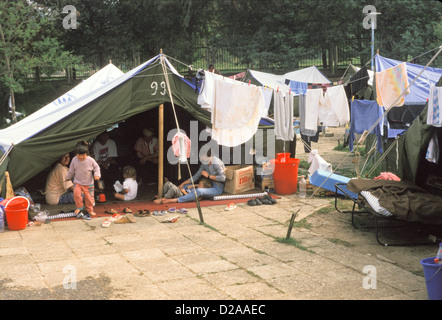 Albania, Tirana, Swimming Pool Camp For Kosovo Refugees. Women And Children In Tent With Laundry Hanging Outside. - Stock Photo
