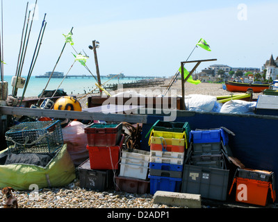 Colourful boxes, pots etc stacked against pier on Worthing beach, view along beach, pier in distance. - Stock Photo