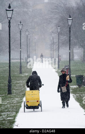 Snowfall makes commuting more challenging but does not stop dogwalkers or mothers taking their small children out - Stock Photo