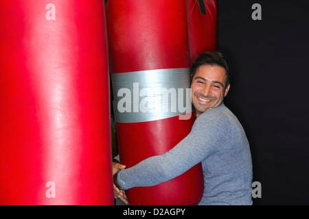 Smiling boxer hugging punching bag - Stock Photo