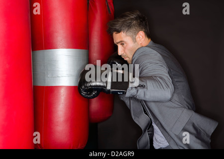 Boxer training with punching bag - Stock Photo