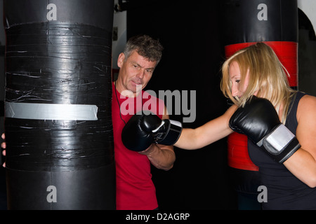 Boxer working with trainer in gym - Stock Photo