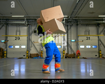 Worker carrying boxes in warehouse - Stock Photo