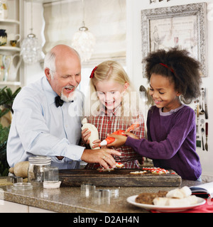 Family baking Christmas cookies together - Stock Photo
