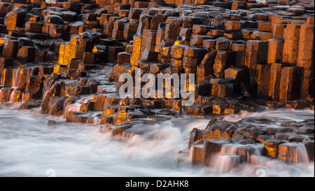 Dramatic late afternoon light and waves splashing on the basaltic rocks from the Giant's Causeway - landmark of - Stock Photo