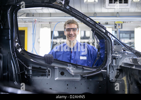 Worker standing by car in factory - Stock Photo